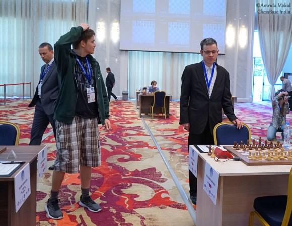 """Kovalyov subito agli onori della cronaca, ma stavolta la questione è extrascacchistica: si presenta ancora in bermuda in sala torneo e il capo-arbitro stavolta interviene e lo invita a rispettare il dress-code. Le cronache (e lo stesso Kovalyov) poi ci dicono di una aggressione verbale da parte di Zurab Azmaiparashvili, organizzatore georgiano della World Cup e """"pezzo grosso"""" FIDE; sta di fatto che Anton decide addirittura di tornarsene a casa, senza ricorrere in appello (il presidente del comitato d'appello è lo stesso Azma…) e rinunciando ai 16.000 $, Foto Chessbase"""
